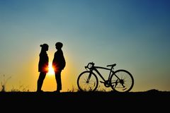 Dating on the sunset. Silhouette of the couple standing hand in hand with bicycle on sunset. Concept dating on the sunset Stock Image