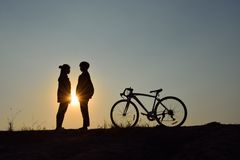 Dating on the sunset. Silhouette of the couple standing hand in hand with bicycle on sunset. Concept dating on the sunset Stock Photo