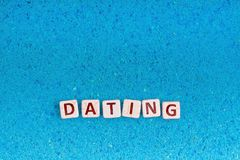 Dating word on stone. Dating word write in square white stone on blue sand, free space for your text royalty free stock images
