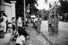 Datki daje w ranku gdy michaelita chodzą ulicami dla jedzenia w Luang Prabang, Laos czarny white zdjęcie royalty free