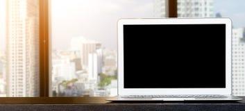 Dator bärbar dator med den tomma skärmen på trätabellen med bakgrunder för kontorsfönstersikt royaltyfri foto