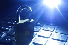 Dator eller dataanalys - hänglåset över ett bärbar datordatortangentbord tonade i blått royaltyfri fotografi