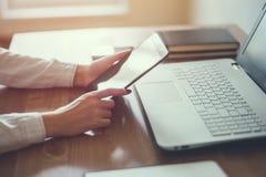 Dator för bärbar dator för hand för affärskvinna funktionsduglig på träskrivbordet Fotografering för Bildbyråer