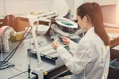 Dator för bräde för härlig kvinnlig tekniker för datorexpert yrkesmässig undersökande i ett laboratorium i en fabrik Royaltyfri Foto