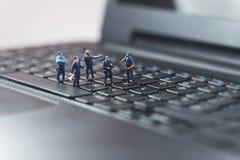 Dator för bärbar dator för miniatyrpolistrupp skyddande begrepp isolerad teknologiwhite Royaltyfri Bild