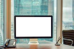 Dator med den tomma skärmen och telefonen på arbetsplatsen in royaltyfria bilder