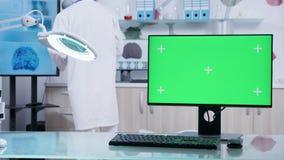Dator med grön skärmåtlöje upp på doktorsskrivbordet stock video