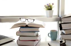 Dator och böcker på den vita affärstabellen arkivfoto