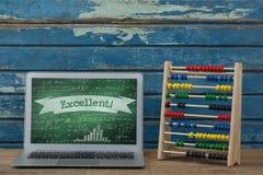 Dator på en skolatabell med skolasymboler på skärmen Royaltyfri Foto