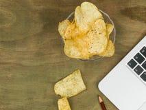 Datorarbetsstation med en Boewl av chips eller potatischien Arkivfoto