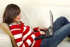 datorbärbar dator genom att använda unga kvinnor Arkivfoto