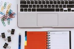Datorbärbar dator med den öppnade anteckningsboken och kontorsgemmen och penna på det vita skrivbordet Arkivbilder