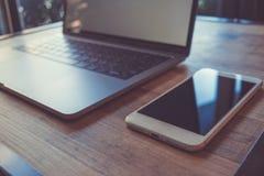 Datorbärbar dator och smart telefon för mobil med den tomma skärmen på trä royaltyfria bilder