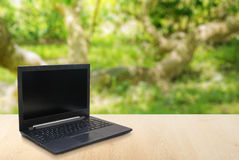 Datorbärbar dator på tabellsuddighetsbakgrunden med bokeh Fotografering för Bildbyråer