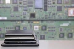 datorbärbar datorbunt En hög av datorer på en ljus tabell mot ljust suddigt grönt digitalt bräde för elektronisk strömkrets royaltyfria foton