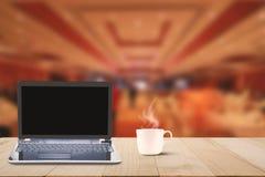 Datorbärbara datorn med den svarta skärmen och den varma kaffekoppen på trätabellöverkant på suddigt hotell övar påtryckningar ba Arkivbilder