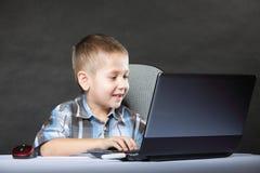 Datorböjelsebarn med bärbar datoranteckningsboken Arkivfoto