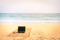 Datorbärbar dator på stranden på tropisk destination Arkivfoto