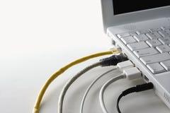 datoren cords den pluggade bärbar dator Fotografering för Bildbyråer