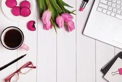 Datoren, exponeringsglas, kaffe och tillbehören i rosa färger färgar på vit fotografering för bildbyråer