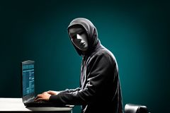 Datoren hacker i den vita maskeringen och hoodien Fördunklad mörk framsida Datatjuv, internetbedrägeri, darknet och cybersäkerhet arkivfoton