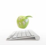 Datoren och ett äpple med världen kartlägger Fotografering för Bildbyråer