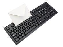 Datoren skrivar med ett kuvert för postar insida. Arkivfoto