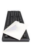 Datoren skrivar, och kuvertet för postar. Arkivfoto