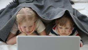 Datorer i liven av moderna barn hållande ögonen på tecknade filmer för liten syskongrupp på bärbara datorn som in ligger på säng stock video