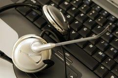 datorhörlurar med mikrofonbärbar dator Arkivfoto