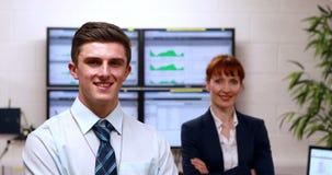 Datorhallkollegor som i regeringsställning ler på kameran stock video