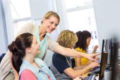 Datorlärare som hjälper kvinnliga studenter royaltyfri bild