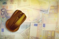 Datormus på bakgrunden av dollar och euro arkivbilder