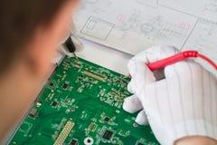 Datorreparationsservice, händer av moderkortet för mantechprovning med hjälpmedel Arkivfoto