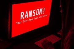 Datorskärm med ransomwareattackvarning i rött och en man K Royaltyfri Fotografi