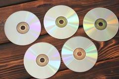 Datorskivor på en träbakgrund royaltyfri fotografi