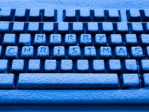 Datortangentbord med glad jul för text på knappar som täckas med upplyst snö av blått neonljus royaltyfri foto