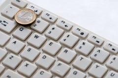 Datortangentbord och ett euromyntslut upp på en vit bakgrund affären coins internetbärbar datorwhite för euroutbyte för härlig va arkivbild