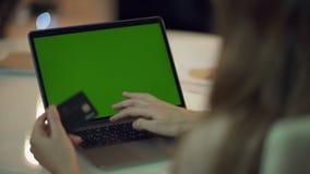 Datos de la tarjeta de crédito de la mujer que mecanografían sobre el ordenador portátil con la pantalla verde metrajes