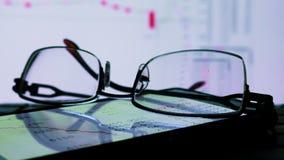 Datos en línea del comercio de la bolsa de acción sobre un monitor y los vidrios almacen de video