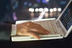 Datos estadísticos del uso del hombre de negocios bajo la forma de gráficos y cartas digitales en el fondo de la noche Imagen de archivo