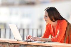 Datos que entran del empresario sobre el ordenador portátil en un balcón fotografía de archivo