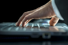 Datos que entran del hombre sobre su ordenador portátil Fotos de archivo libres de regalías