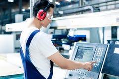 Datos que entran del trabajador en máquina del CNC en la fábrica fotografía de archivo libre de regalías