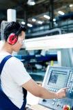 Datos que entran del trabajador en máquina del CNC en la fábrica imagen de archivo