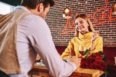 Datte romantique La femme blonde regarde son ami tout en mangeant dans le restaurant images libres de droits