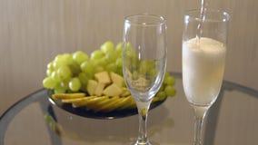 Datte romantique Renversement du champagne en verres sur une table avec le fruit banque de vidéos