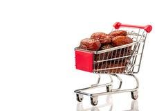 Dattelpalmefr?chte in einem Einkaufswagen, lokalisiert auf einem wei?en Hintergrund Platz f?r Text isolat lizenzfreies stockbild