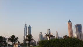 Dattelpalmen und hohe Aufstiegs-Turm-Gebäude, Sheikh Zayed-Straße in Dubai Lizenzfreie Stockbilder