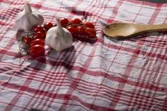 Datterino-Tomaten, Knoblauch und hölzerner Löffel auf einer Tischdecke Stockfotos